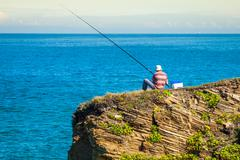 fisherman on the rocks,ribadeo, spain - stock photo