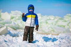Cute little boy outdoors standing on winter beach - stock photo