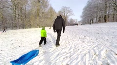 Father and son on a winterday pulling the sleigh Stock Footage