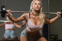 sexy woman doing exercise barbell squat - stock photo