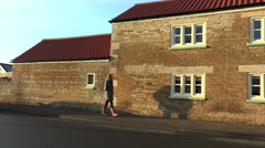 Teenage girl walking past old stone house Stock Footage