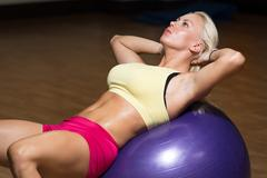 Young female doing abs workout Stock Photos