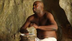Shirtless Black man plays drum in cave in Cuba Stock Footage