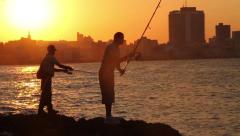 Silhouetted Men fish in Malecon, Havana, Cuba at sunset Stock Footage