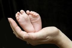 five week old baby feet held in mothers hand. - stock photo