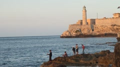 Fishermen in bay of Havana with Morro Castle in Back Ground Stock Footage