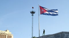 Police woman stands by Cuban Flag in Plaza de la Revolucion, Havana, Cuba Stock Footage