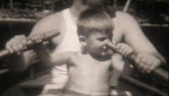 1554 - dad teaches his son to row a boat - vintage film home movie Stock Footage