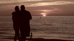 Silhouette of romantic couple watching gorgeous sunset Stock Footage