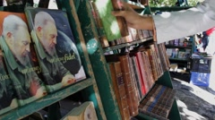 Books of Fidel Castro in Park, hand picks one up in Havana Stock Footage