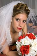 autumn bride with bouquet and leafs laying on her bed. - stock photo