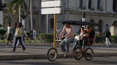 Bicycle Taxi, Old American Cars pass by in Havana street, Cuba Stock Footage