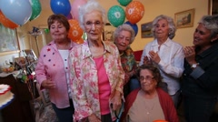 Family celebrates birthday party for a 100 year old lady with cake and candles Stock Footage