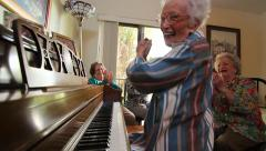 Older lady plays piano with friends, finishes to applause - stock footage