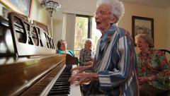 Older lady plays piano and sings in Spanish with friends Stock Footage