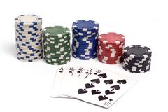 a royal straight flush hand with colored poker chips. - stock photo