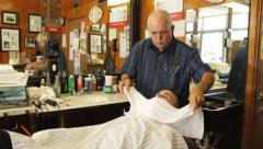 Barber puts hot towel on customer's face for shaving in Old Fashion Barber Shop - stock footage