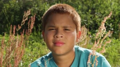 Biracial kid looks at camera with different expressions in a field - stock footage