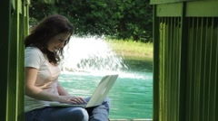 Young woman sitting on dock with laptop, typing, fountain in B/G Stock Footage