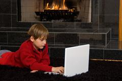 boy at fireplace on computer. - stock photo