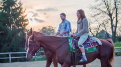 Middle age couple on a horseback riding with sunset in the back  - stock footage