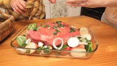 Zoom out from meat dish as two women prepare it and putting it in  oven Stock Footage