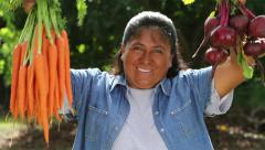 Latino indigenous woman holds up Radish and Carrots and smiles to camera Stock Footage