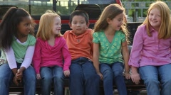 Multi racial kids sit in back of  pickup truck laughing playfully in Slow Motion - stock footage