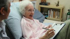 Old lady happily signs Last Will and Testament in bed with female Stock Footage