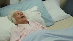 Old lady takes her last breath, dies in bed. Dolly shot Stock Footage