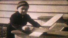 1552 - boys use their carpenter skills to cut wood - vintage film home movie - stock footage