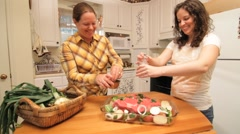 Women preparing meat dish and putting it in the oven Stock Footage