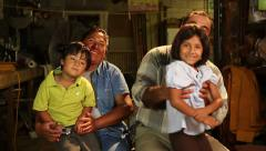Mexican, Latino Family of four, poses to camera smiling inside a garage Arkistovideo