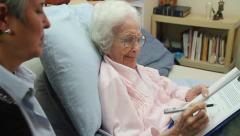 Old lady in bed signs Last Will and Testament angry, dolly shot Stock Footage