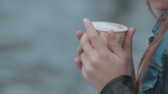 Close up of beautiful mysterious girl sitting by the sea with a cup of coffee Stock Footage