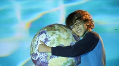kid with curly hair and glasses hugs globe of Planet Earth, smiles to camera - stock footage
