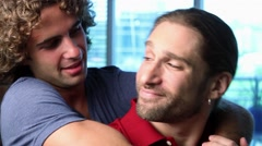 Close Up of two young gay men embrace and smile to camera Stock Footage
