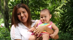 Young Hispanic, Latina Mom holds and kisses baby, smiles to camera Stock Footage