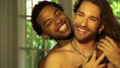 Black and White gay men embrace smile to camera Stock Footage
