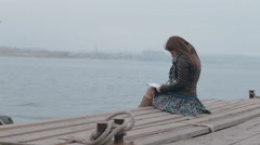 Romantic girl in skirt sitting on the pier near the sea and drawing Stock Footage