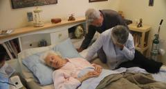 Old lady dies in bed, family members gather crying, Dolly shot. - stock footage