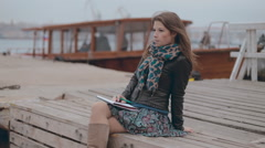 Close up of a mysterious smiling girl in a skirt sitting on the pier near the Stock Footage
