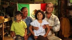 Mexican family of 4 poses siting and smiling to camera in front of Mexican flag Stock Footage
