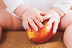 Little baby is holding red apple. hands of small child. healthy food Stock Photos