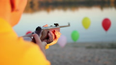 Rifle shooting at balloons near the river Stock Footage