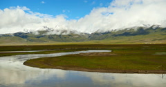 4k timelapse clouds mass rolling over Tibet mountain,River flowing the prairie. Stock Footage