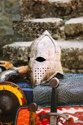 Protective helmet with a visor on medieval knight - stock photo