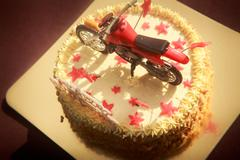 birthday cake decorated with motorcycle and red stars - stock photo