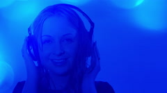 Stock Video Footage of Attractive young woman listening to music, blue background