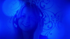 Young woman listening music, blue light backgrounds Stock Footage